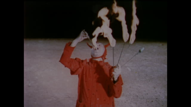 vidéos et rushes de 1958 man dressed as devil swallows fire as male audience members laugh - perception sensorielle