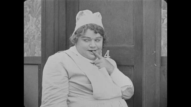 vídeos y material grabado en eventos de stock de 1918 man dressed as female nurse flirts with male doctor - estación de enfermeras