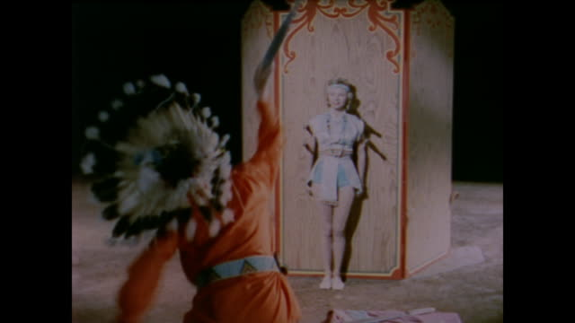 vídeos de stock, filmes e b-roll de 1958 man dressed as indian throws axes at a woman in circus routine demonstrating the sensation of sight - balançando