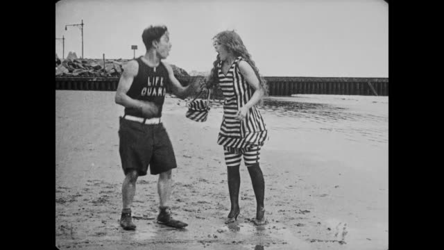 1917 man (buster keaton), dressed as lifeguard, takes woman (alice mann) by hand and runs down the beach with her and falls - buster keaton stock videos and b-roll footage