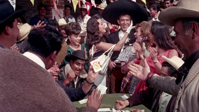 man dressed as mariachi and fancy looking woman approached betting table among a multitude they placed their bet against another man in mariachi... - leisure games stock videos & royalty-free footage