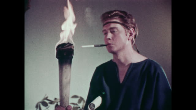 1967 man dressed as roman carries flaming torch, lighting his cigarette as he runs out of shot - toga stock videos and b-roll footage