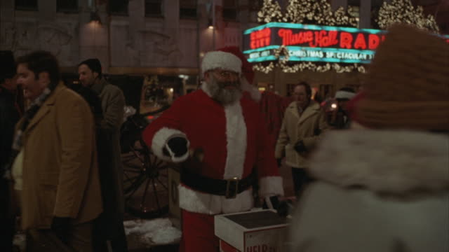 a man dressed as santa claus rings a bell energetically in front of radio city in new york. - radio city music hall stock videos & royalty-free footage