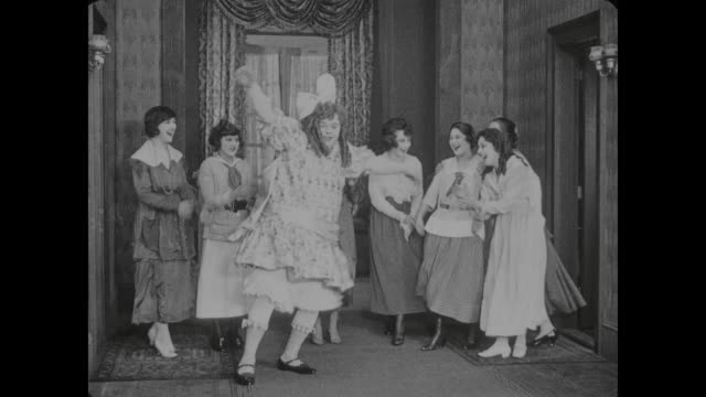 1917 Man (Fatty Arbuckle) dressed as woman dances in hallway before a small crowd