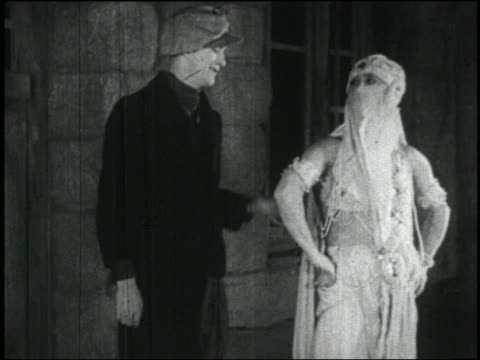 b/w 1926 man dressed as woman in veil (ben turpin) slaps other man outdoors - 1926年点の映像素材/bロール