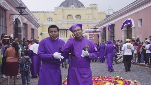 vídeos de stock e filmes b-roll de man dressed for catholic celebration talking by phone. he wears purple traditional costume typical of the lent easter celebration in antigua guatemala during parade. - religião