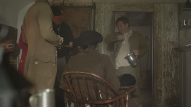 a man dressed in a colonial costume pours drinks for other colonialists in a tavern. - the past stock videos & royalty-free footage