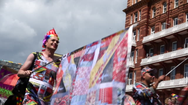 A man dressed in a homemade patchwork costume carries a patchwork Union Jack flag whilst parading in the Brighton Gay Pride Parade 2017