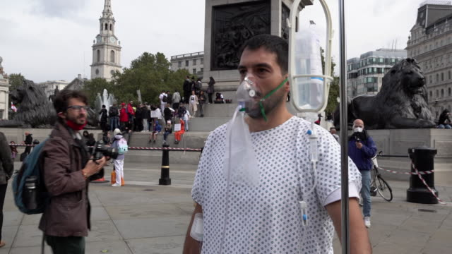 man dressed in a hospital gown, wearing an oxygen mask and wheeling a intravenous drip walks past trafalgar square where a coronavirus conspiracy... - トラファルガー広場点の映像素材/bロール