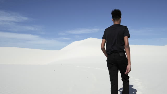 man dressed in black walks in desert, wide - wide stock videos & royalty-free footage
