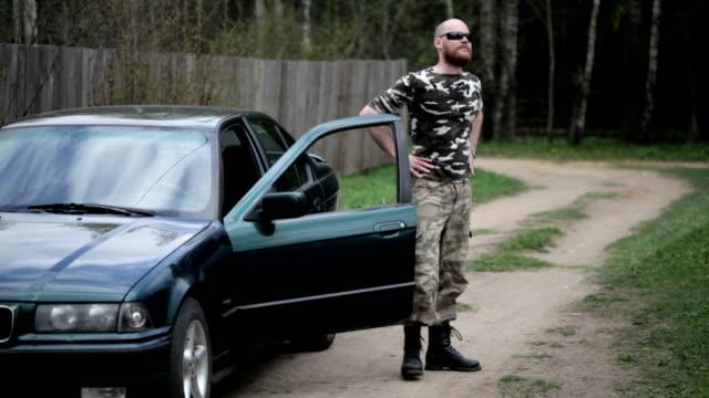 甚平を着た男性カモフラージュ外の車 - 降り立つ点の映像素材/bロール