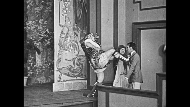 vidéos et rushes de 1919 man (buster keaton), dressed in drag, jumps off of the stage and knocks a jeering audience member out of his chair, when the jeering man stands up, man (fatty arbuckle) kicks him and pulls other man back onto the stage - donner un coup de pied