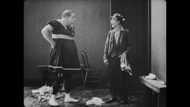 1917 man (fatty arbuckle), dressed in drag, throws clothes at man (buster keaton) in bath house - fatty arbuckle stock videos and b-roll footage