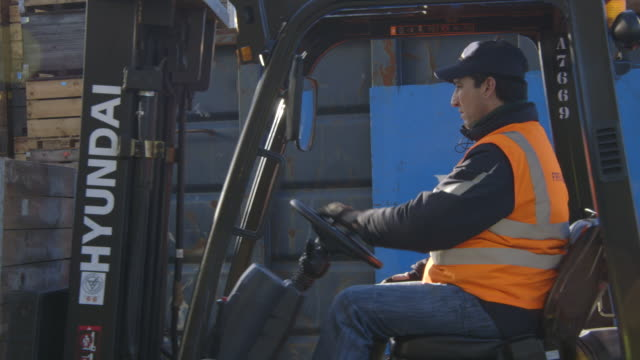 A man dressed in orange high-visibility wear operates a forklift vehicle at a fruit distribution centre in Kent, UK.