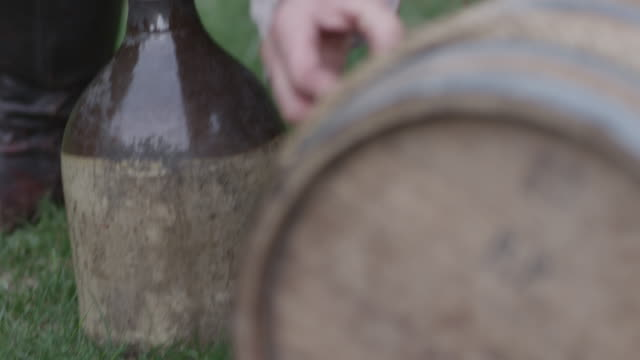 a man dressed in revolutionary war era clothing tries to get the stopper out of a barrel on the ground beside a stoneware jug. - cork stopper stock videos & royalty-free footage