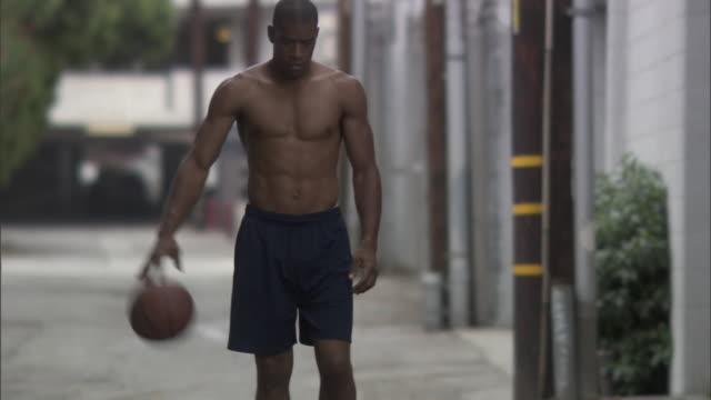 ms td tu man dribbling basketball along sidewalk / culver city, california, usa - にじみ出す点の映像素材/bロール