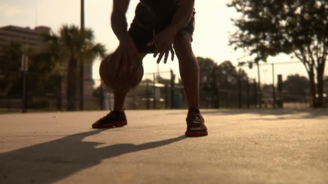 slo mo ms shaky td tu man dribbling basketball on street court, jacksonville, florida, usa - jacksonville florida video stock e b–roll