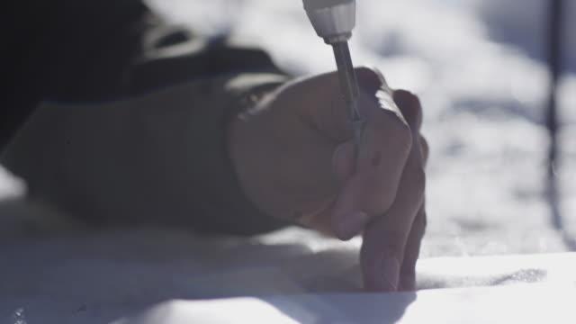 stockvideo's en b-roll-footage met man drills screwdriver into ice, close up - gereedschap