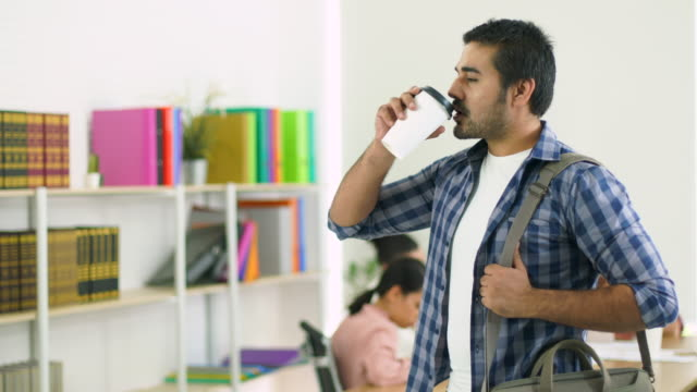 Man Drink Coffee In Office With Blur People Background