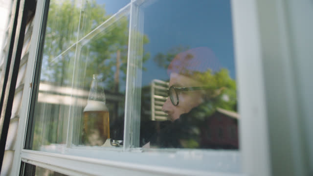 slo mo. cu man drinking a beer as he looks out his home window. - bierflasche stock-videos und b-roll-filmmaterial