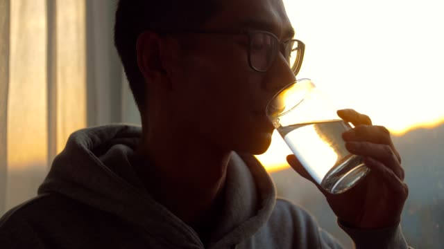man drinking a cup of water by window in the morning - drinking water stock videos & royalty-free footage