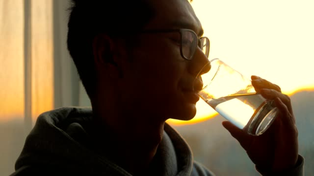 man drinking a cup of water by window in the morning - young men stock videos & royalty-free footage