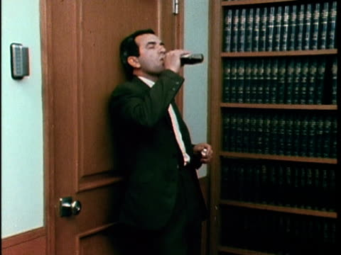 1967 MONTAGE Man drinking alcohol in office, Los Angeles, California, USA, AUDIO