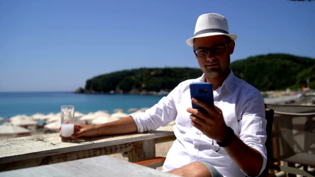 man drinking and texting on beach terrace - summer reading stock videos & royalty-free footage