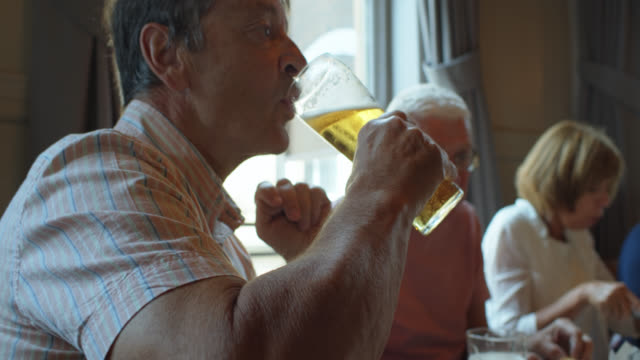 man drinking beer at pub lunch with friends - senior men stock videos & royalty-free footage