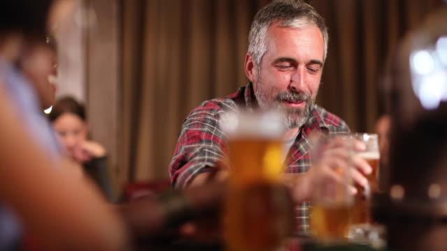 mann trinkt bier, während er mit seinen freunden nach der arbeit an der bar entspannt - pint stock-videos und b-roll-filmmaterial
