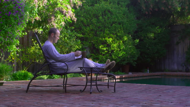 WS, PAN, Man drinking coffee and leafing through newspaper at poolside, Hollywood, California, USA