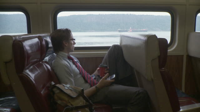 ws man drinking coffee and using mobile phone in train / new york city, new york, usa - 2009 stock videos & royalty-free footage