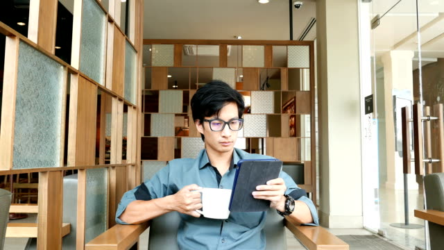 Man drinking coffee and using tablet in a coffee shop