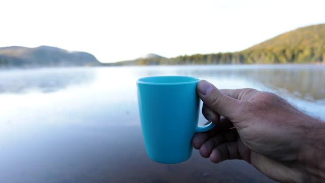 mann trinkt kaffee am see in camping im herbst - besonderes lebensereignis stock-videos und b-roll-filmmaterial