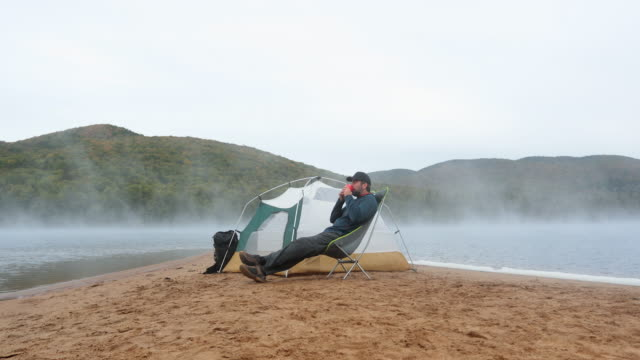 man drinking coffee by the lake in camping - outdoor chair stock videos & royalty-free footage
