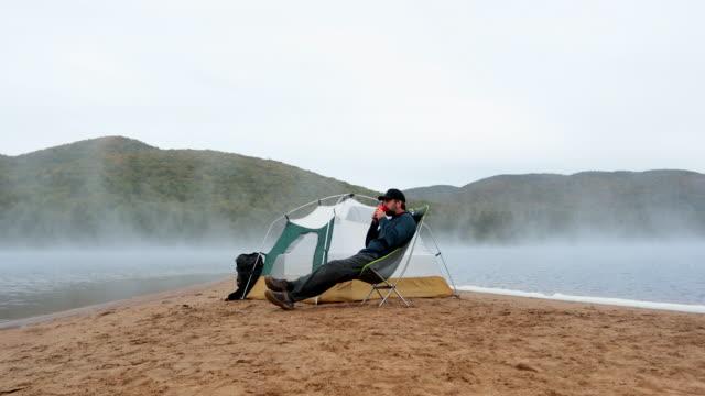 mann trinkt kaffee am see in camping - besonderes lebensereignis stock-videos und b-roll-filmmaterial