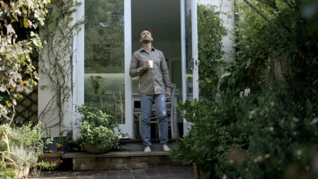 vidéos et rushes de man drinking coffee outside home and walking towards garden. - boisson chaude