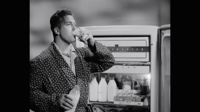 man drinking milk while standing next to refrigerator in kitchen - bathrobe stock videos & royalty-free footage