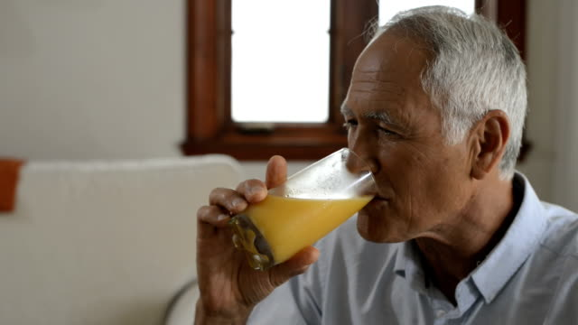 man drinking orange juice - juice drink stock videos & royalty-free footage