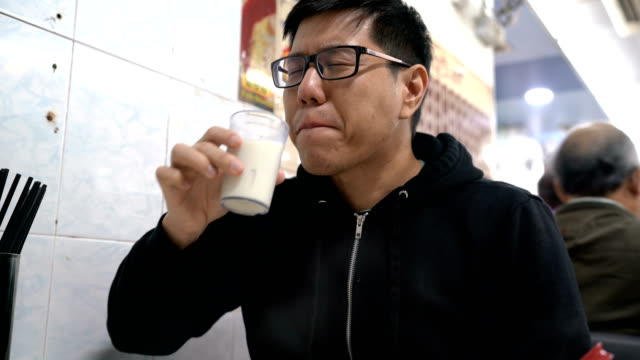 man drinking soy bean milk - soy milk stock videos and b-roll footage