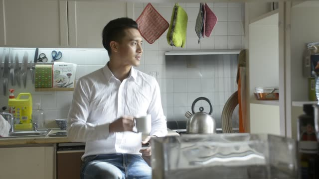 man drinking tea in kitchen - oven mitt stock videos and b-roll footage