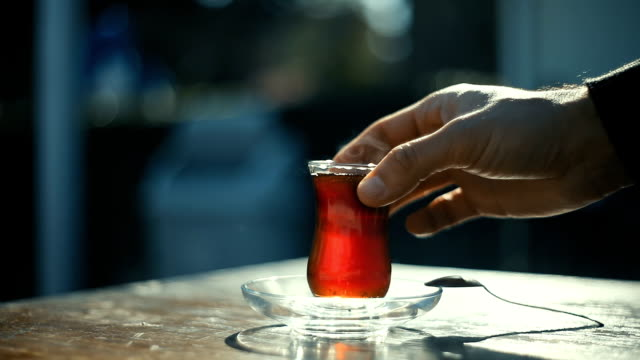 man drinking turkish tea with special cup on a sidewalk tea house table with unrecognizable blurry people on the background - black tea stock videos & royalty-free footage