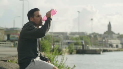 man drinking water after exercising outdoors - sitting stock videos & royalty-free footage