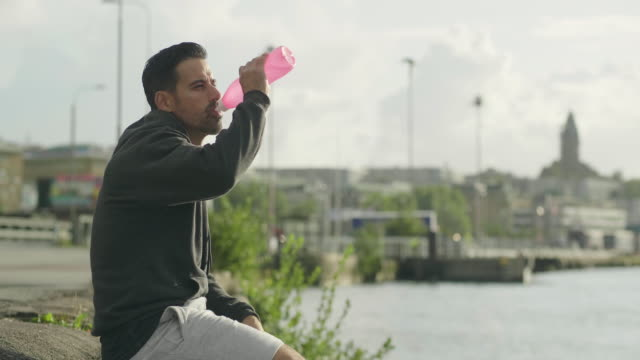 man drinking water after exercising outdoors - harbor stock videos & royalty-free footage
