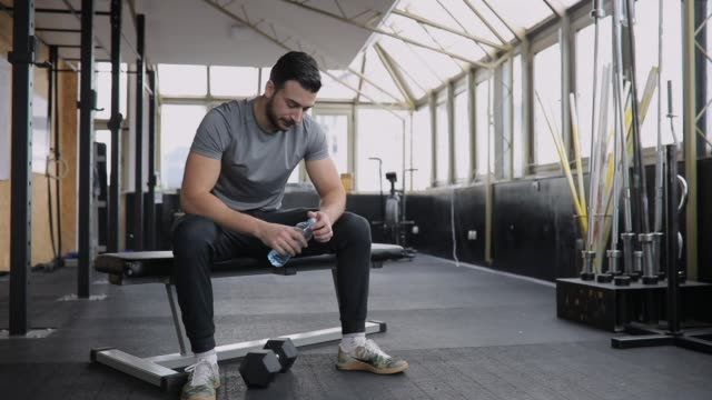 man drinking water after training - gym stock videos & royalty-free footage