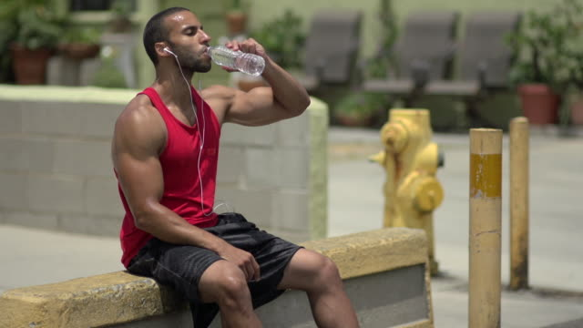 A man drinking water and resting after a intense workout. - Slow Motion