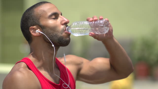stockvideo's en b-roll-footage met a man drinking water and resting after a intense workout. - slow motion - pauze nemen