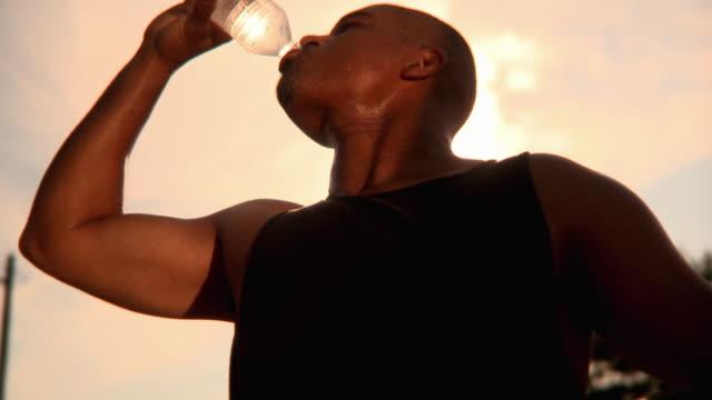 vidéos et rushes de cu shaky la man drinking water bottle outdoors, jacksonville, florida, usa - sueur