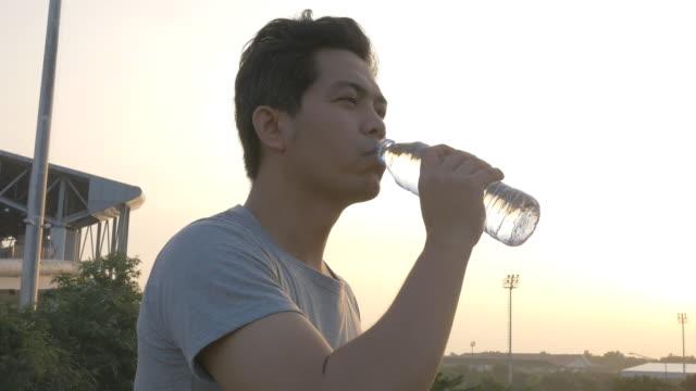 vídeos de stock, filmes e b-roll de homem bebendo água em garrafa de correr ao ar livre - sedento
