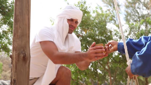 man drinking water in the oasis in desert - trinkwasser stock-videos und b-roll-filmmaterial